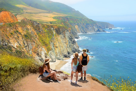 a group of hikers look over a bluff at a Pacific Ocean beach near Los Angeles, California