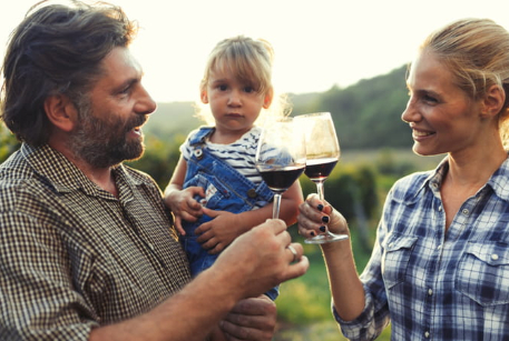 two people toasting wine glasses while holding child