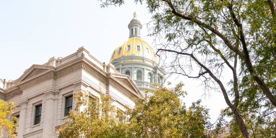 view of the golden dome of the Colorado State Capitol Building from the outside lawn