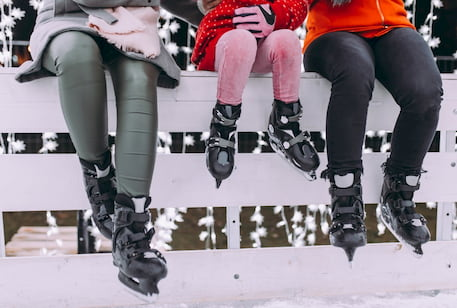 two adults and a child sit on a fence around a skate rink while wearing ice skates