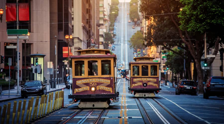 two San Francisco cable cars pass each other on a hilly street