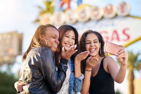 friends take a selfie in front of the las vegas sign
