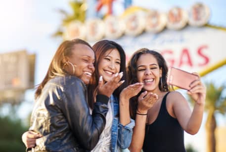 A group of young women taking photos in front of the Las Vegas sign