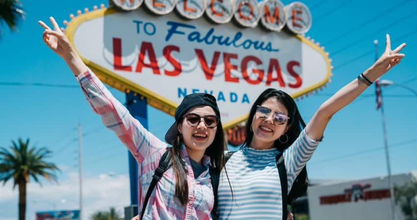 two women posing with the peace hand sign in front of the Las Vegas Sign