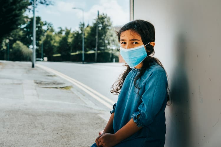 Little girl at bus stop wearing face mask