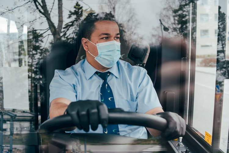 Bus driver wearing gloves and mask