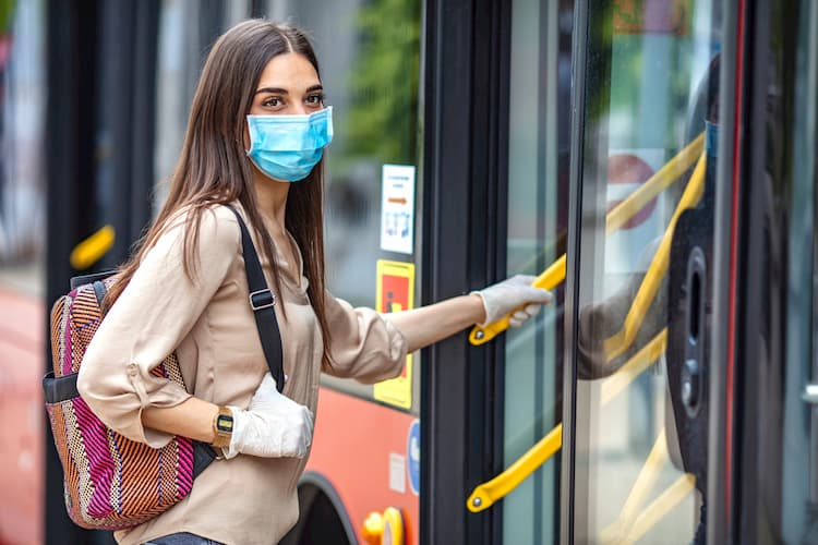 Woman boarding bus in gloves and mask