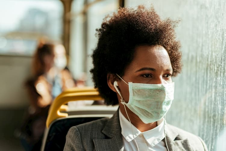 Woman wearing mask while listening to music on bus