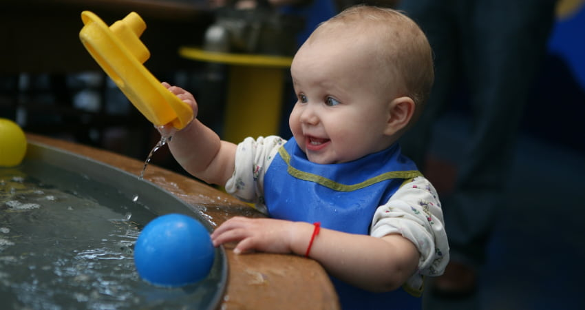 a small toddler plays at a water table in a children's museum