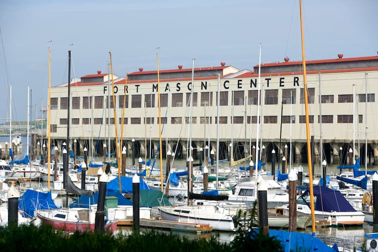 The Fort Mason Center building from the outside with boats in front of it