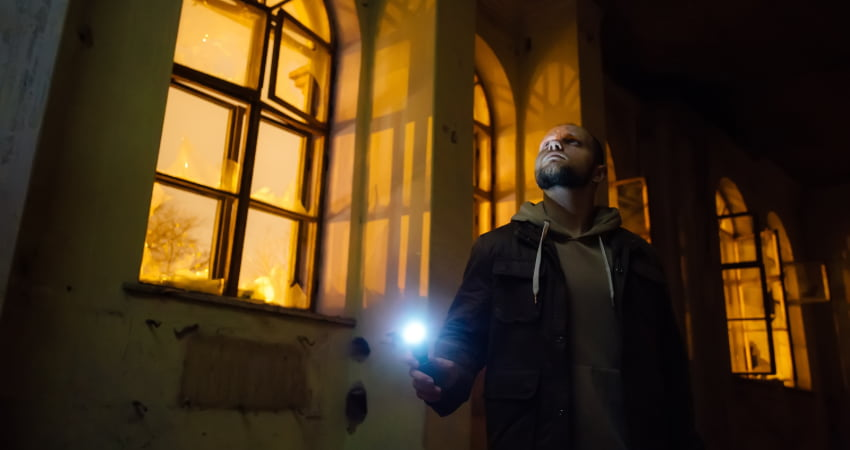 A ghosthunter explores an abandoned building, shining a flashlight and walking past tall windows