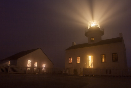 The Old Poma Lighthouse on a foggy night, beacon shining into the sky