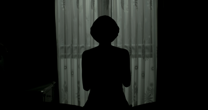 The silhouette of a woman standing in front of a curtained window