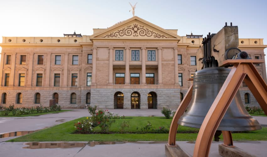 The exterior of the Arizona Capitol Museum, a big iron bell in the foreground