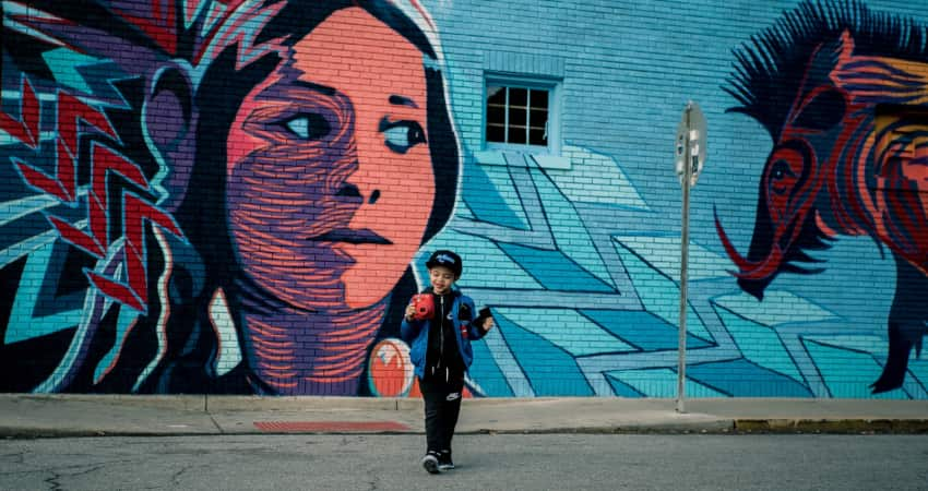 A child holds a camera and stands in front of a bright mural. The mural depicts a Native American woman and a boar on a blue background