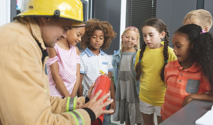 A firefighter shows a fire extinguisher to a class of curious children