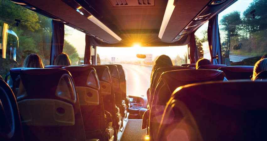 The inside of a charter bus while driving in the sunset