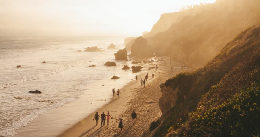An aerial view of people walking along El Matador Beach at sunset