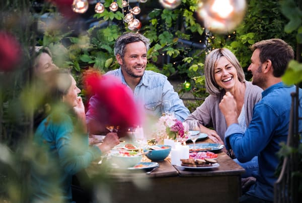 A group of dinner guests eat food in a garden dinning space