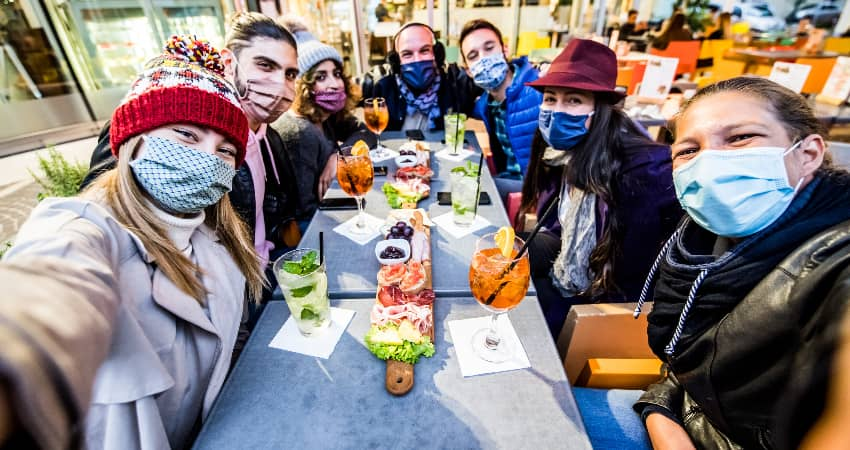 A group of dinner guests in masks enjoy appetizers in an outdoor restaurant