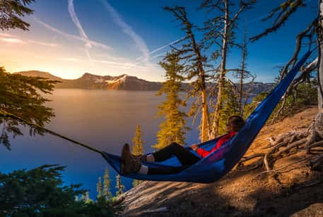 A hiker in a hammock overlooking the lake at Crater Lake National Park