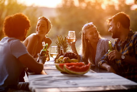A group of friends dine at an outdoor table at sunset