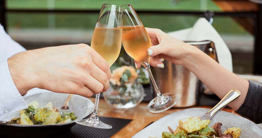 A couple toasts glasses of wine in an outdoor dining venue