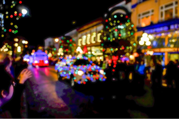 a blurred image of a car with holiday lights going down a street with lots of colorful light displays