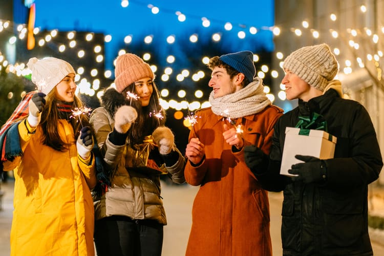 four friends hold sparklers while wearing coats and hats with snow and holiday lights in the background
