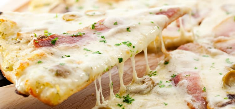 a slice of white pizza being slowly pulled away from the pie with cheese strings stretching