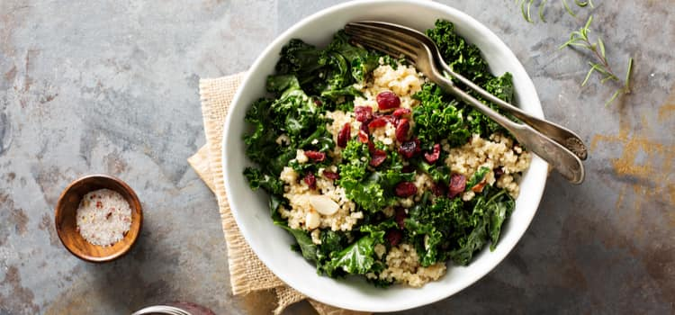 a kale salad with dried cranberries and nuts on top
