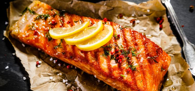 a fresh piece of grilled salmon with seasonings and lemon slices on top