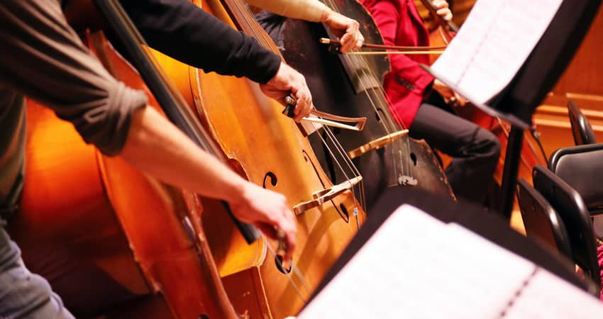 Close up of an orchestra playing instruments