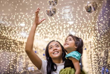 A woman holding a child while walking under glittering lights