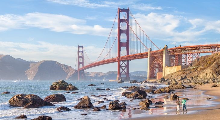 view of the Golden Gate Bridge from Baker Beach in San Francisco. 3 beachgoers walk the sand in the foreground, with the bridge looming in the background