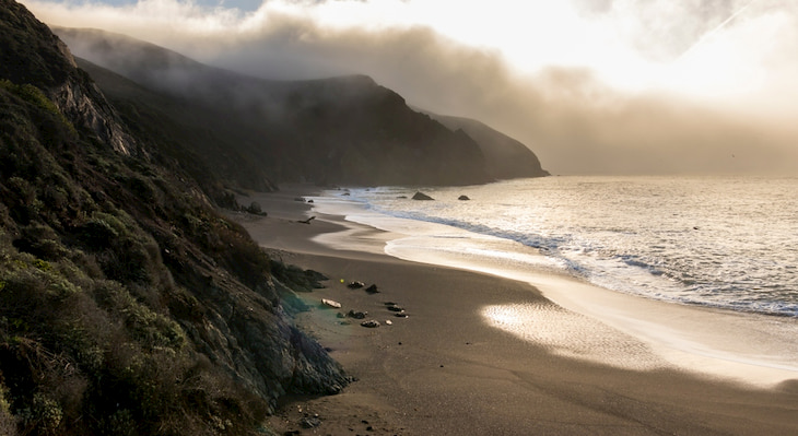 the sun rises over Black Sands Beach In Sausalito, California