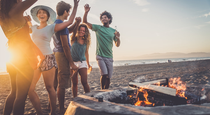 five friends gather around a fire pit at Ocean Beach in San Francisco