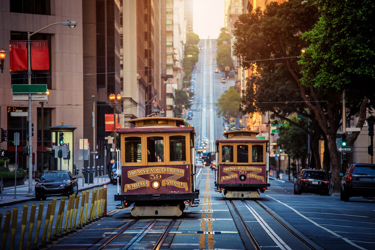 vintage cable cars moving down a narrow san francisco street